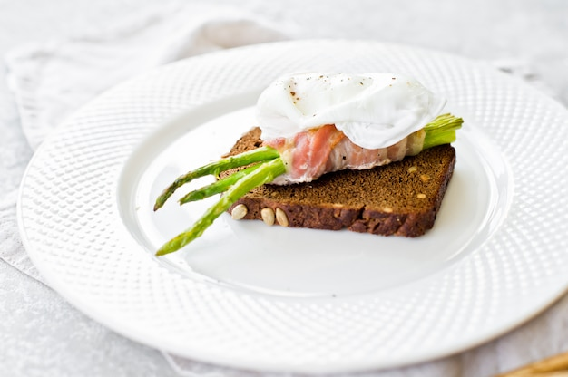 Toast with poached egg and grilled mini asparagus in bacon.