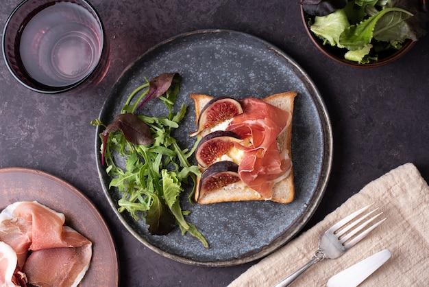 生ハムとイチジクのトースト、イタリアンハムとリコッタチーズのクロスティーニ、暗い背景での軽食、クローズアップ。