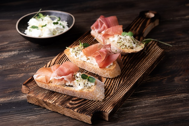 Toast with prosciutto ricotta and microgreens, ham crostini on a dark wooden background, rustic style.