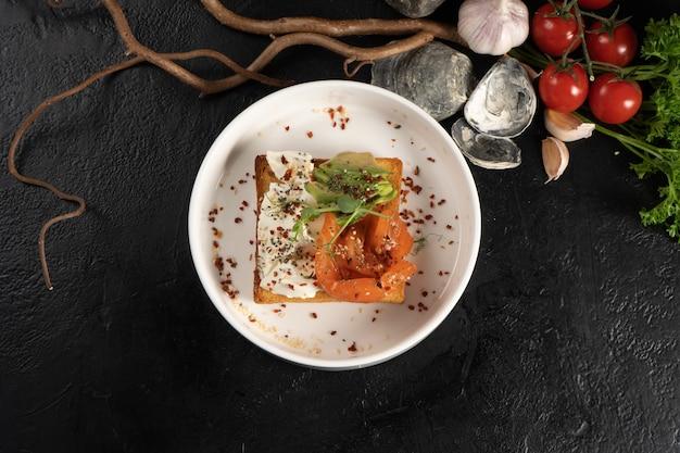 Тост с лососем, авокадо и сливочным сыром. холодный завтрак из рыбы, овощей, тостов и сливочного сыра со специями