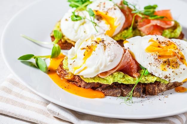 Тост с лососем, яйцом-пашот и авокадо на белой тарелке.