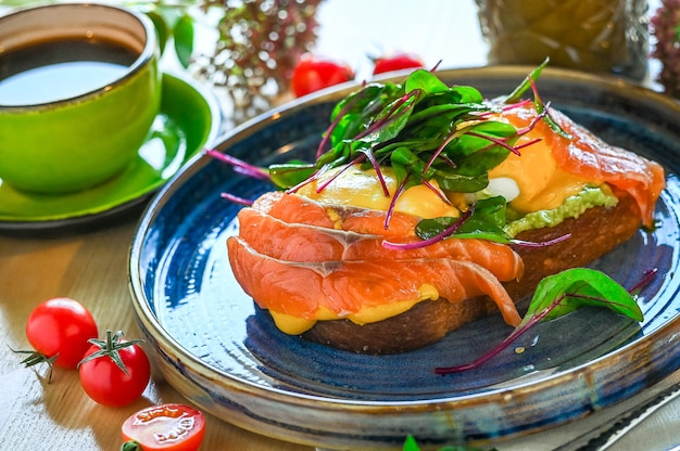 Toast with salmon, poached egg and avocado on a plate. breakfast at the restaurant