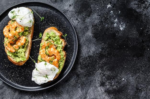 Toast with shrimp, prawns, avocado and poached egg. black background