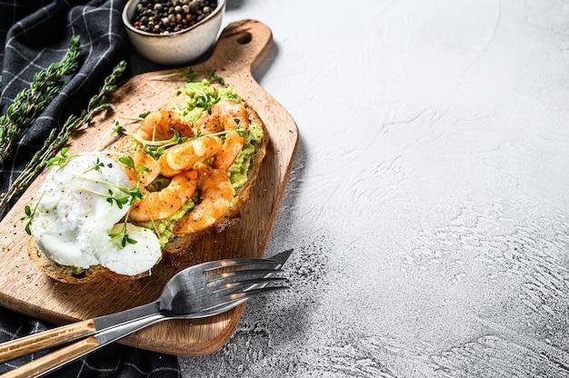 Toast with shrimp, prawns, avocado and poached egg. gray background