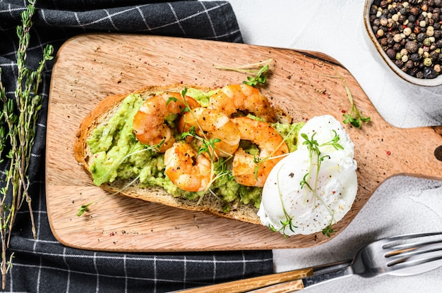 Toast with shrimp, prawns, avocado and poached egg. gray background.