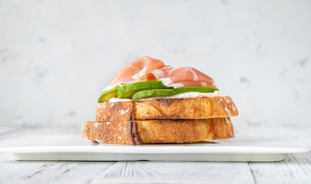 Toast with slices of avocado, prosciutto and cream cheese