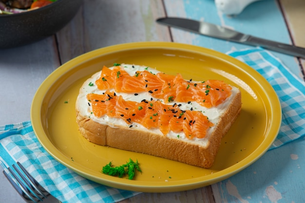 木製のテーブルにスモークサーモンとクリームチーズを添えてトースト
