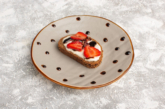 Toast with strawberry and sour cream inside brown plate on grey