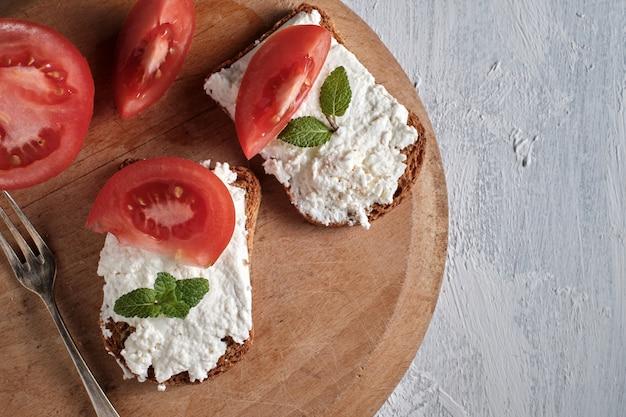 Тост с белым сыром и листьями мяты с ломтиками помидора, вид сверху