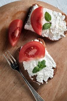 Тост с белым сыром и листьями мяты с ломтиками помидора