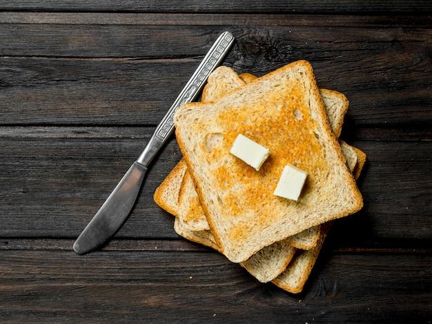 구운 빵과 버터. 나무 배경.