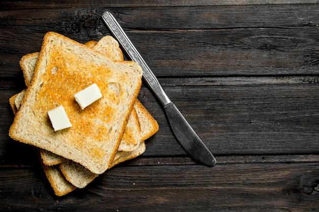 トーストしたパンとバター。木製の背景に。