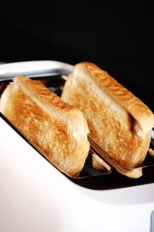 어두운 대리석 위에 구운 빵과 토스터기