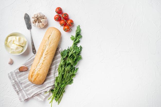 마늘과 허브 재료를 넣은 구운 빵 바게트, 흰색 돌 탁자 배경, 위쪽 전망 평면, 텍스트 복사 공간