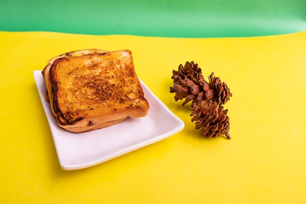 黄色と緑の紙の背景にトウヒの花と白いプレートのトーストパン。朝食のトースト。横の写真