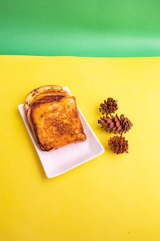 黄色と緑の紙の背景にトウヒの花と白いプレートのトーストパン。朝食のトースト。縦の写真