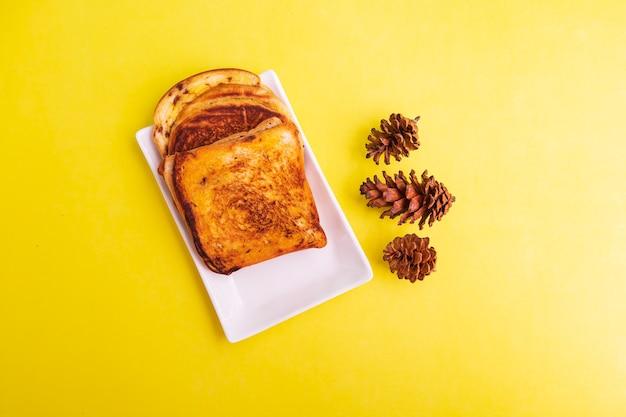 黄色い紙の背景にトウヒの花と白いプレートのトーストパン。朝食のトースト。横の写真