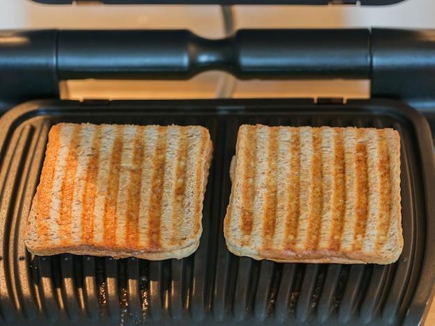Поджаренные ломтики хлеба на электрическом гриле. вкусный хрустящий тостовый хлеб после запекания