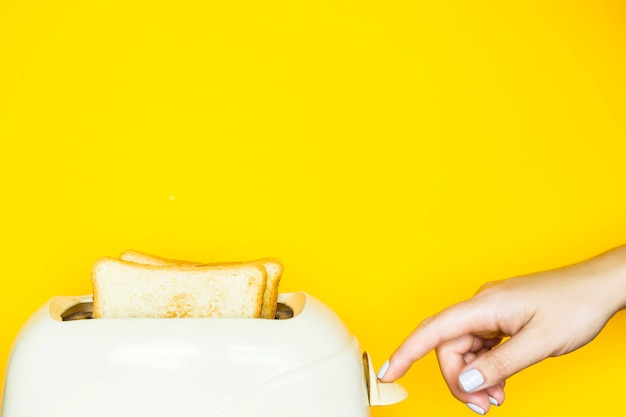 Toasted bread sticks out of the toaster on a yellow background