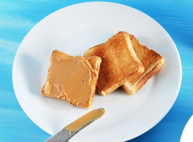 Toasted bread toast with peanut butter and a plate