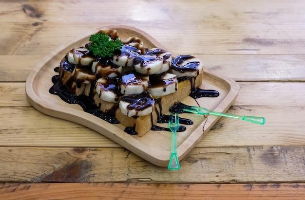 スライスしたバナナをトッピングし、木製のテーブルに置いた木製のトレイにチョコレートソースをトッピングしたトーストしたパン。コピースペースのある正面図。