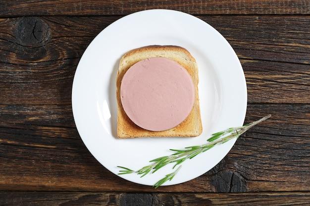 소박한 나무 테이블에 삶은 소시지를 곁들인 구운 빵, 위쪽 전망