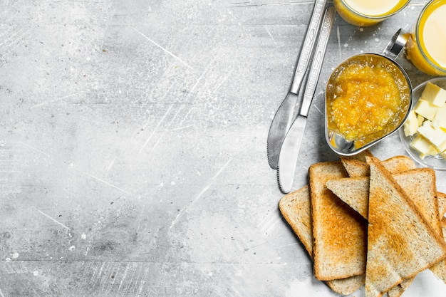 バターとオレンジジャムのトーストしたパン。素朴な背景に。