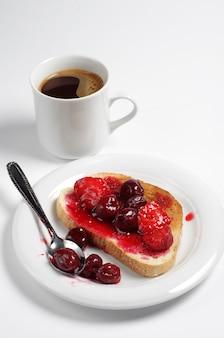 흰색 배경에 통조림 체리, 딸기, 커피 한 잔을 곁들인 구운 빵