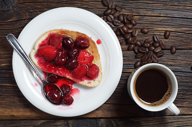 통조림 체리, 딸기, 커피 한 잔을 나무 배경에 넣은 구운 빵. 평면도