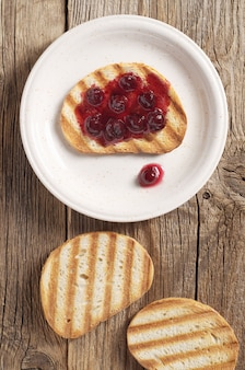 テーブルの上の皿にチェリージャムとトーストしたパン