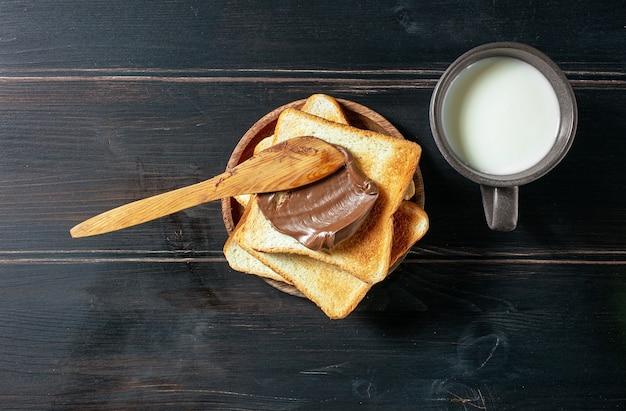 素朴な木製のキッチンテーブル、上面図にチョコレートクリームと新鮮なミルクのカップでトーストしたパン