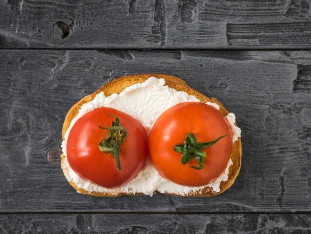 Поджаренный хлеб с творогом и помидорами на деревянном столе. концепция здорового питания. вид сверху плоской планировки.