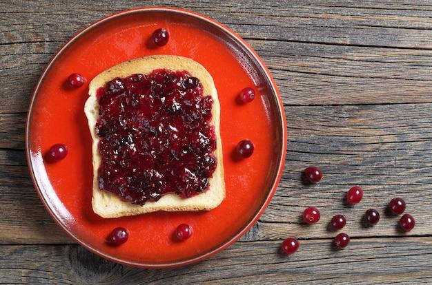 Поджаренный хлеб с клюквенным вареньем и ягодами на красной тарелке