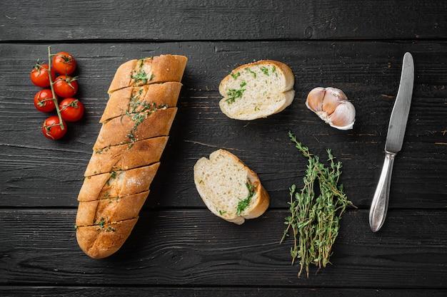 마늘과 허브 세트를 곁들인 구운 빵, 검은색 나무 테이블 배경, 평면도