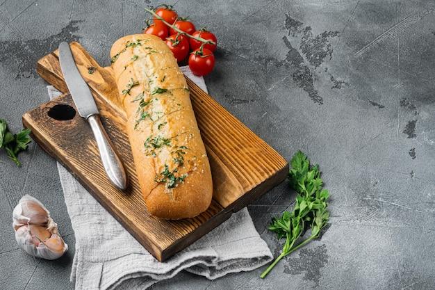 회색 돌 테이블 배경에 마늘과 허브를 넣은 구운 빵, 텍스트 복사 공간
