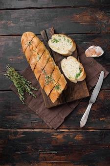 마늘과 허브 세트를 넣은 구운 빵, 오래된 어두운 나무 테이블 배경, 위쪽 전망 플랫 레이, 텍스트 복사 공간