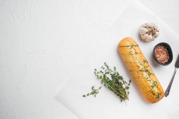 마늘과 허브를 넣은 구운 빵, 흰색 돌 탁자 배경, 위쪽 전망 평면, 텍스트 복사 공간