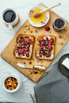 Toasted bread with honey, cream cheese, red fruit jam and coffee