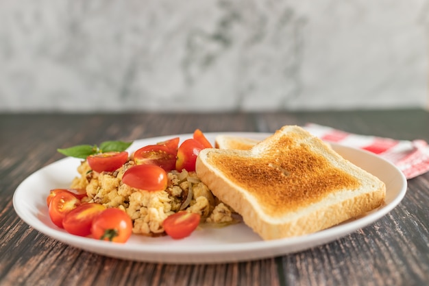 Toasted bread with scrambled eggs and cherry tomato