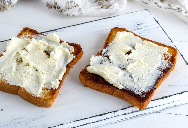 Toasted bread with soft curd on a white wooden board