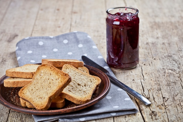 Toasted cereal bread slices on grey plate and jar with homemade cherry jam