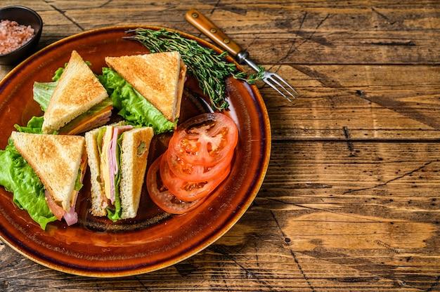 Поджаренные бутерброды club со свининой, сыром, помидорами и листьями салата на тарелке. деревянный фон.