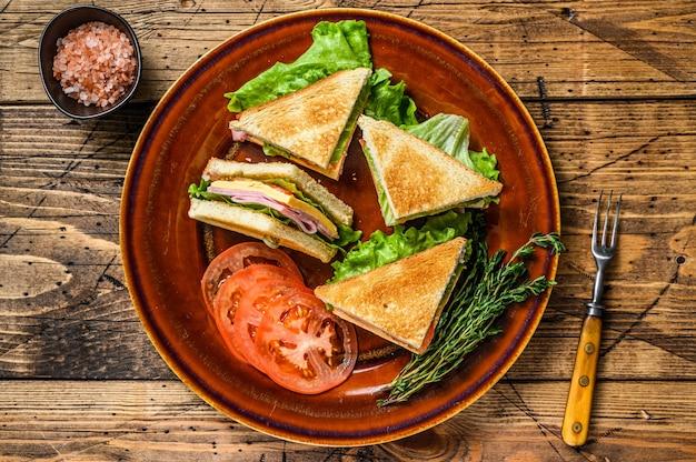 ポークハム、チーズ、トマト、レタスを皿にのせたトースト クラブ サンドイッチ。