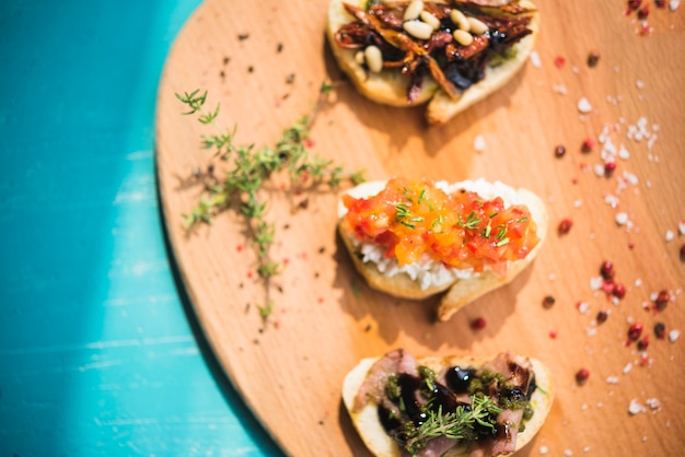 Toasted sandwiches with thyme; peppercorn and salt on wooden board