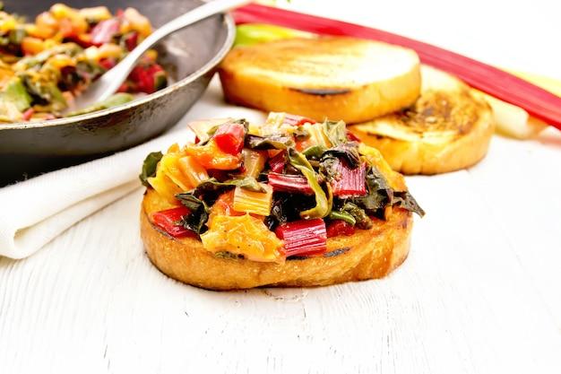 明るい木の板の背景に緑豊かなビート、タマネギ、オレンジの煮込みパンのトーストスライス
