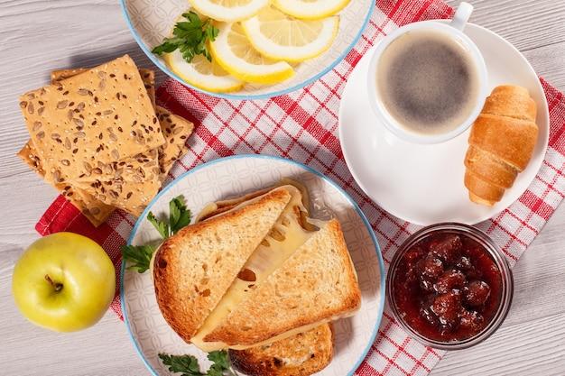 Поджаренные ломтики хлеба с сырным яблочным печеньем с цельнозерновыми семечками нарезанный лимон