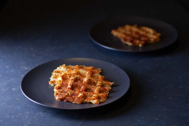 Toasted viennese zucchini waffles on two black plates on a dark