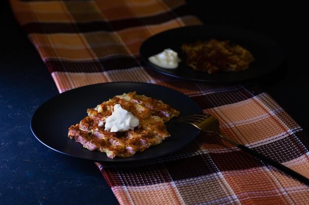 Жареные венские вафли из цуккини со сметанным соусом на двух черных тарелках