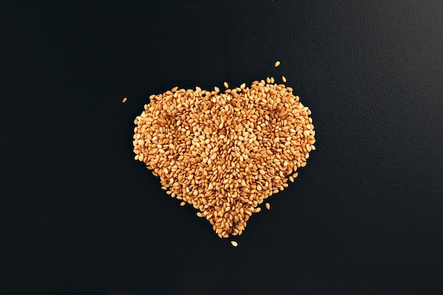 Toasted white sesame seeds arranged in a shape of heart on a smooth black table surface