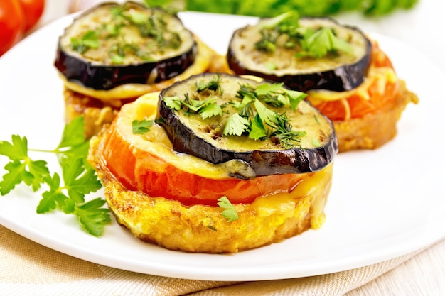 卵、トマト、チーズ、ナスのパンのスライスでトーストし、テーブルの上のリネンナプキンのプレートにディルとパセリを振りかけます